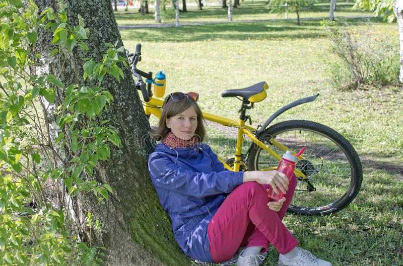 Flicka, n?r att ha ridit en cykel som huka sig ned av ett tr?d f?r att vila royaltyfri fotografi