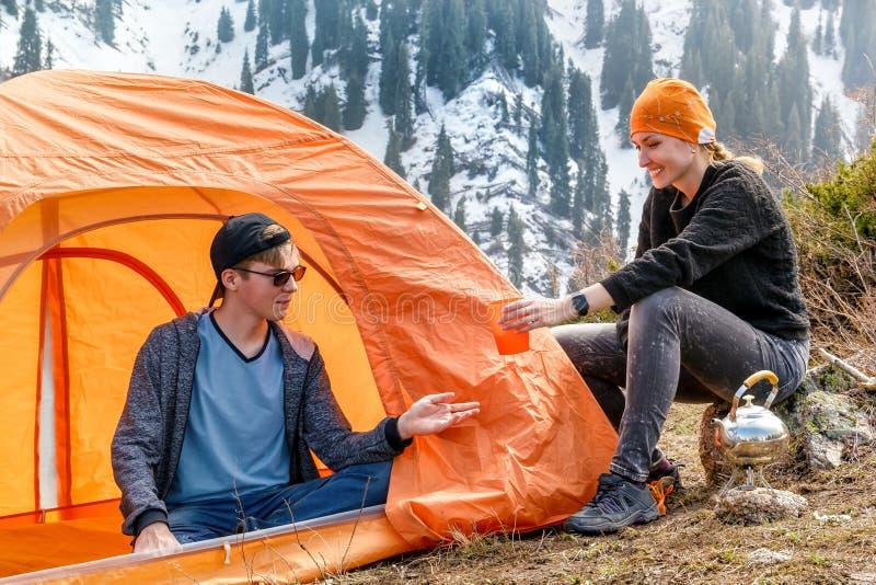 Flicka och en grabb på ett stopp med ett turist- tält som dricker te eller kaffe på en bakgrund av snö-korkade berg för skog Mött arkivbild