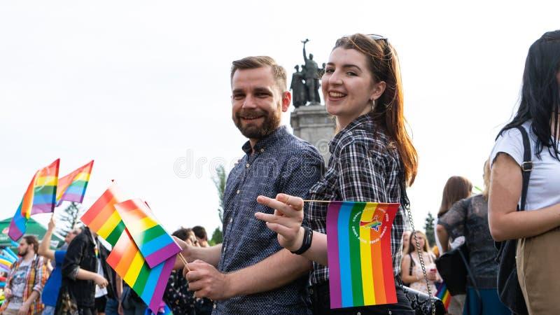 Flicka och grabb med regnbågeflaggan i deras händer i en stolthetfestival i Sofia, Bulgarien arkivfoton