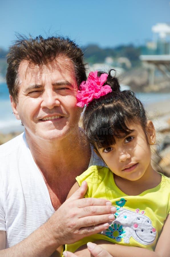 Flicka och hennes fader vid havet arkivbild