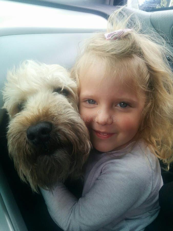 Flicka och hennes le för hund fotografering för bildbyråer