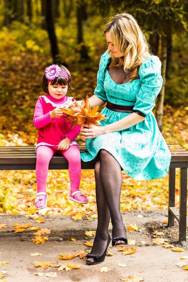 Flicka och hennes moder som utomhus spelar med höstliga lönnlöv Behandla som ett barn flickan som väljer guld- sidor royaltyfri bild