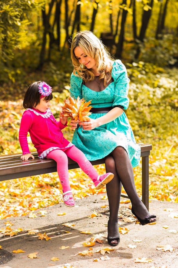 Flicka och hennes moder som utomhus spelar med höstliga lönnlöv Behandla som ett barn flickan som väljer guld- sidor arkivfoto