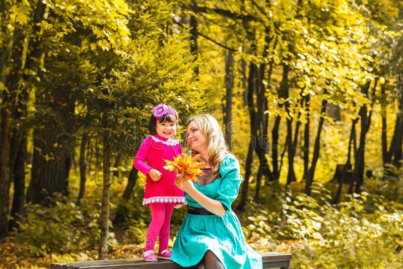 Flicka och hennes moder som utomhus spelar med höstliga lönnlöv Behandla som ett barn flickan som väljer guld- sidor royaltyfria foton