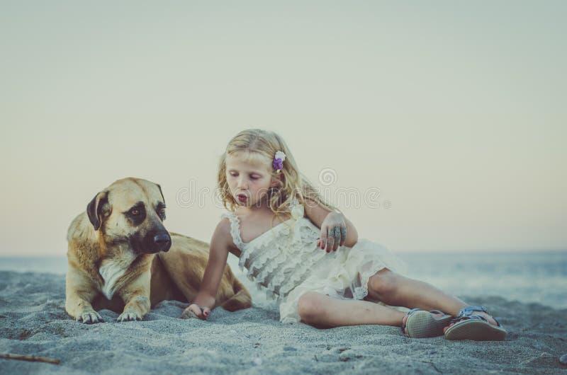 Flicka och hund som ligger i stranden royaltyfria foton