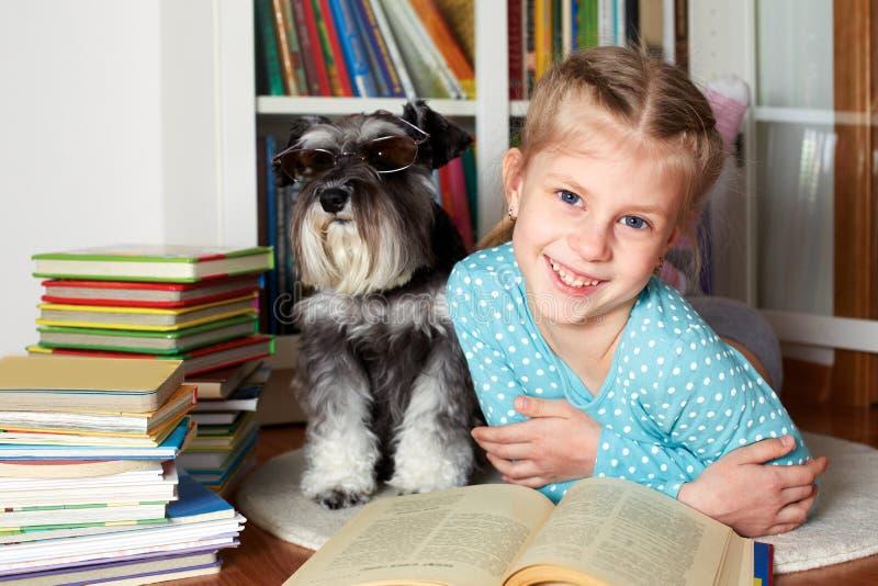 Flicka- och hundläseböcker royaltyfria bilder