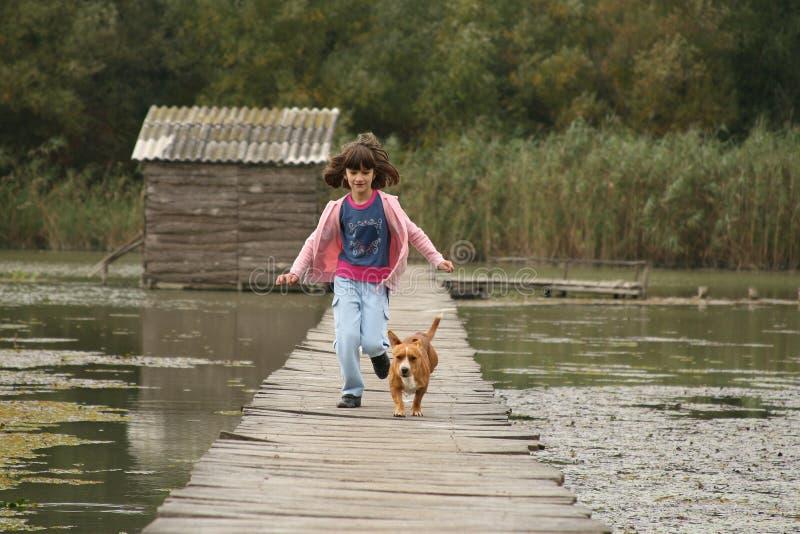 Flicka- och hundspring fotografering för bildbyråer