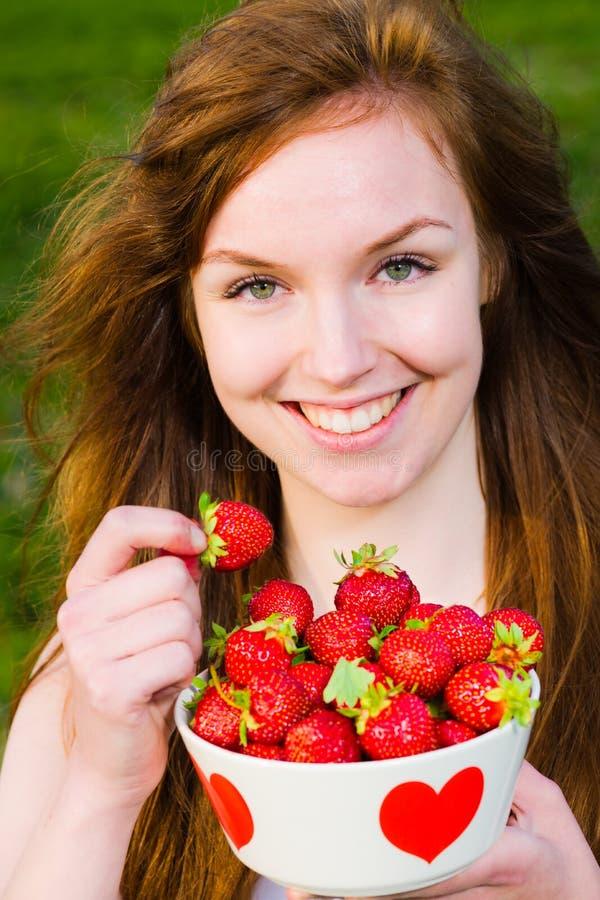 Flicka och jordgubbar royaltyfria bilder