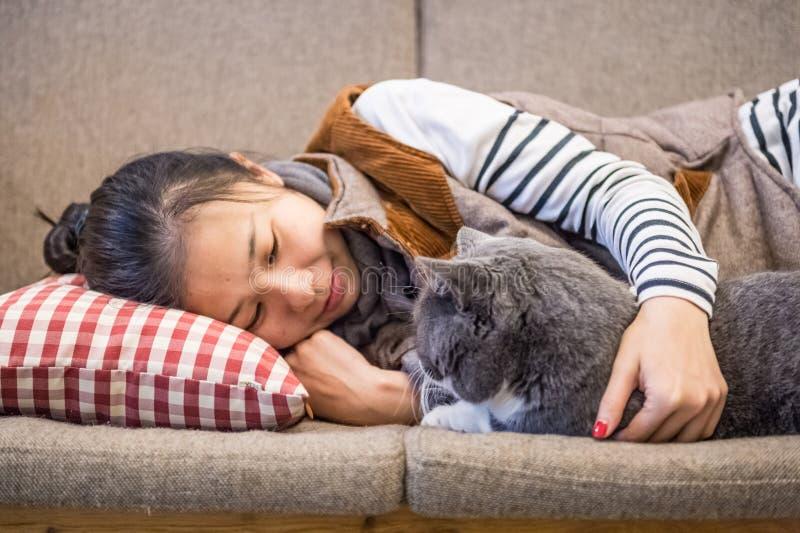 Flicka och katt som sover på soffan royaltyfri fotografi