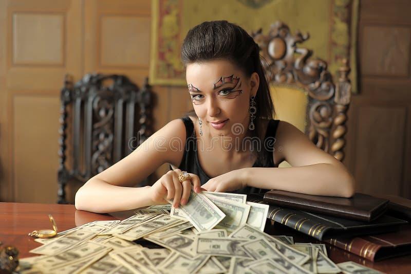 Flicka och många dollar arkivbilder