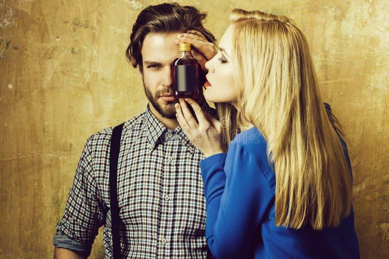 Flicka och macho posera med likörflaskan fotografering för bildbyråer
