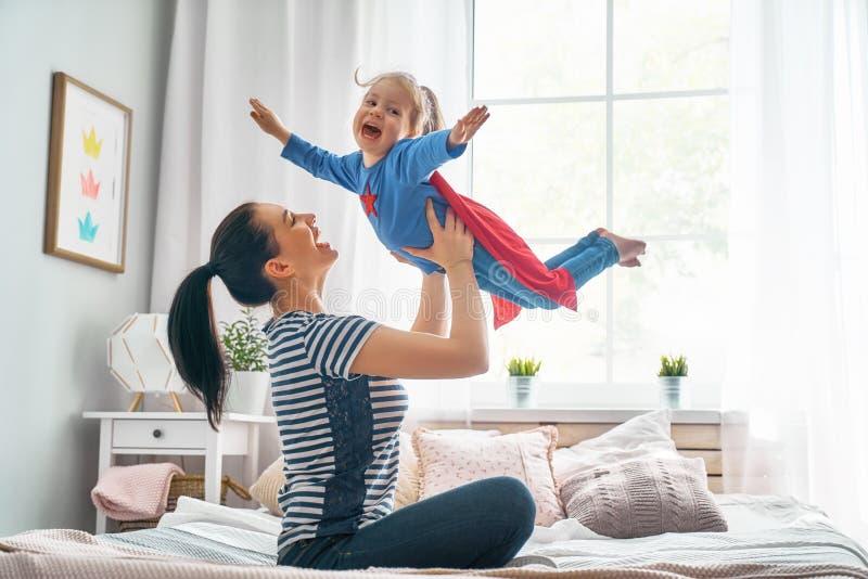 Flicka och mamma i Superherodräkt royaltyfria bilder