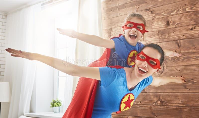 Flicka och mamma i Superherodräkter arkivbilder