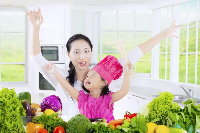 Flicka och mamma med grönsaker i kök royaltyfria bilder