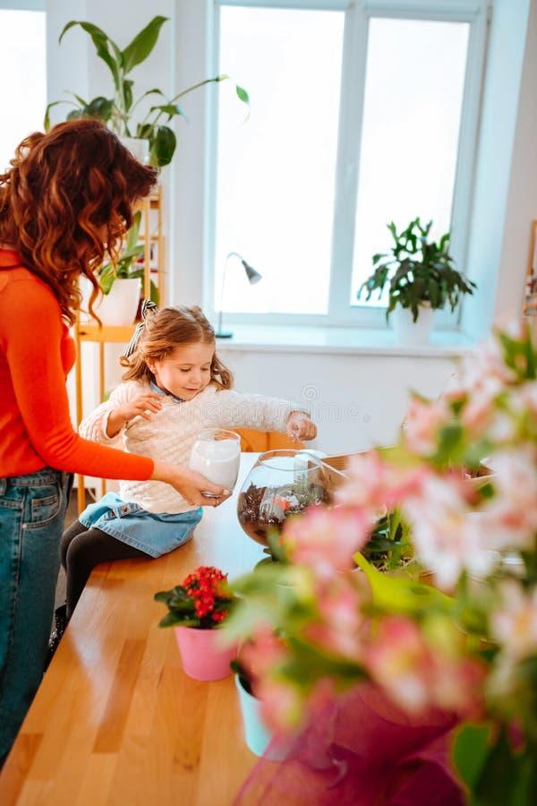 Flicka och mamma som tillsammans sätter något socker in i kakturs arkivbilder