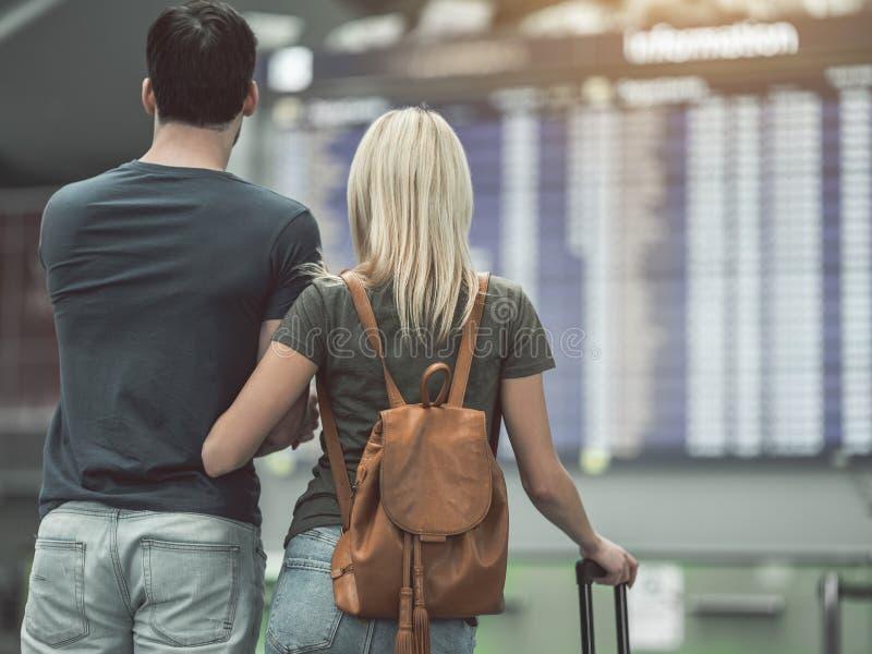Flicka och man som håller ögonen på på flygplatsbrädet royaltyfri foto