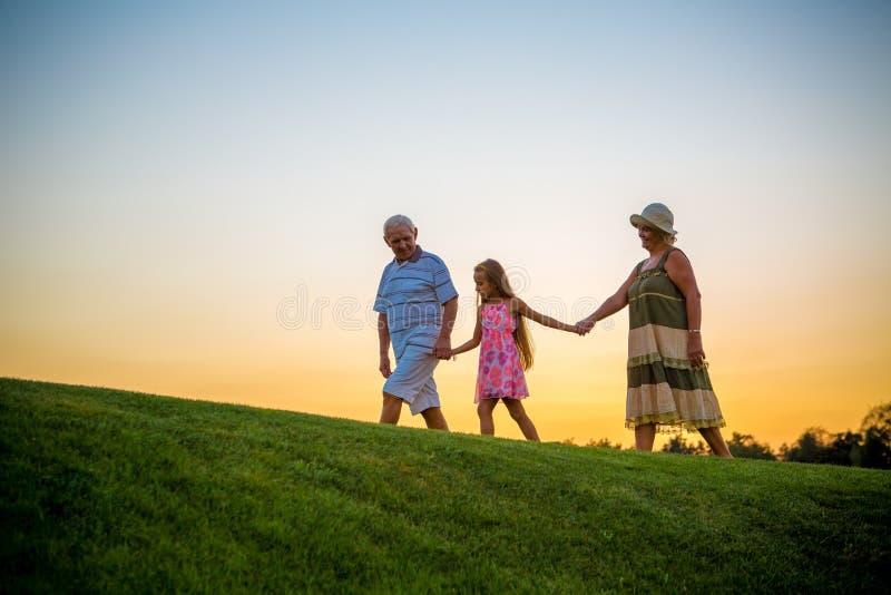 Flicka och morföräldrar, solnedgånghimmel royaltyfria foton