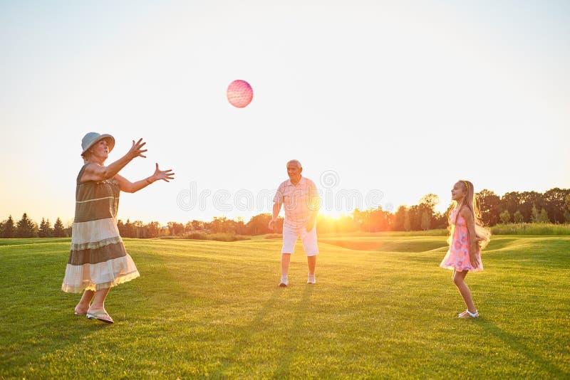 Flicka och morföräldrar som spelar bollen arkivfoto