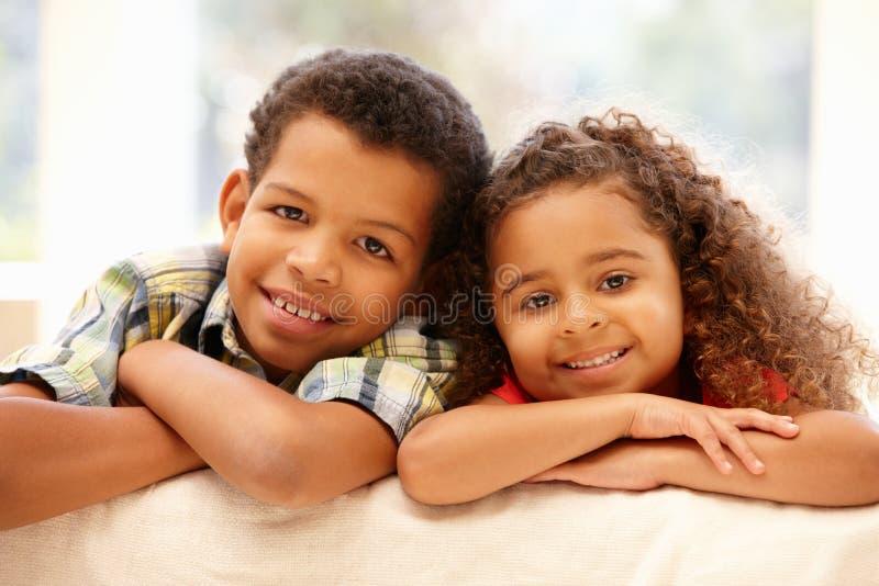 Flicka och pojke för blandat lopp hemma arkivbilder