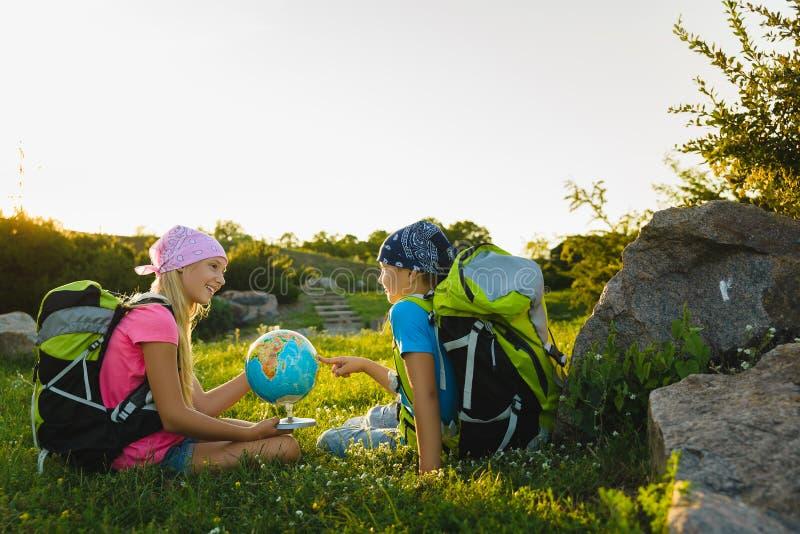 Flicka och pojke med ryggsäckar och att vila för jordklot som är utomhus- Affärsföretag loppbegrepp royaltyfria foton