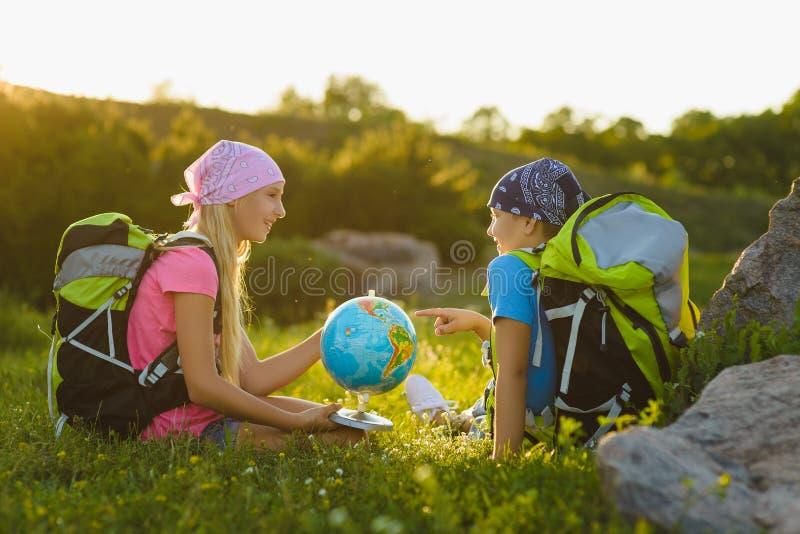Flicka och pojke med ryggsäckar och att vila för jordklot som är utomhus- Affärsföretag loppbegrepp royaltyfri bild