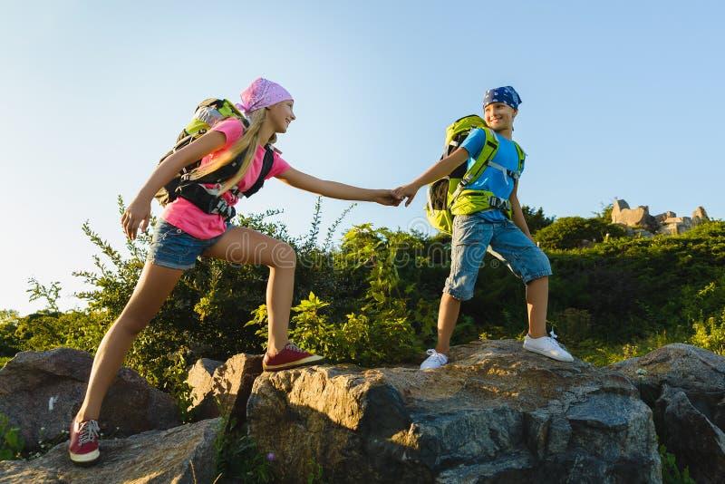 Flicka och pojke med ryggsäckar i kullar Affärsföretag lopp, turismbegrepp royaltyfri foto