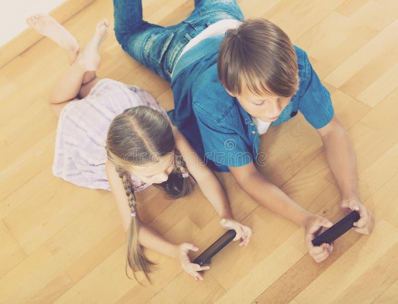 Flicka och pojke som begraver i mobiltelefoner arkivbilder