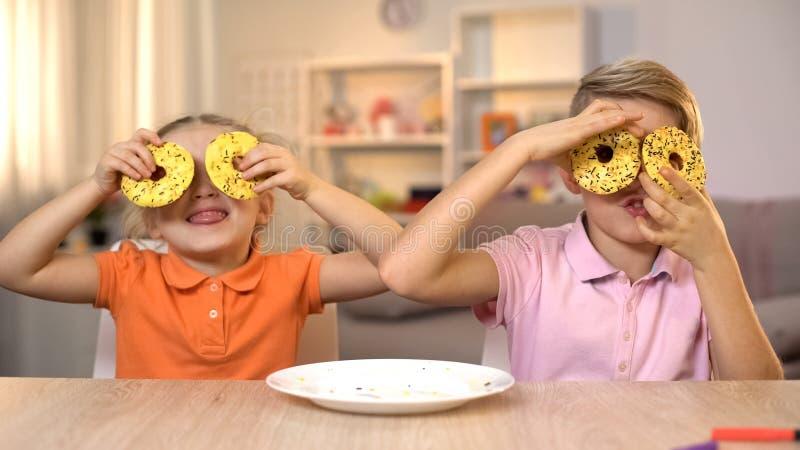 Flicka och pojke som rymmer den gula donutsframdelen av ?gon och att ha det roliga sjukliga mellanm?let royaltyfri foto