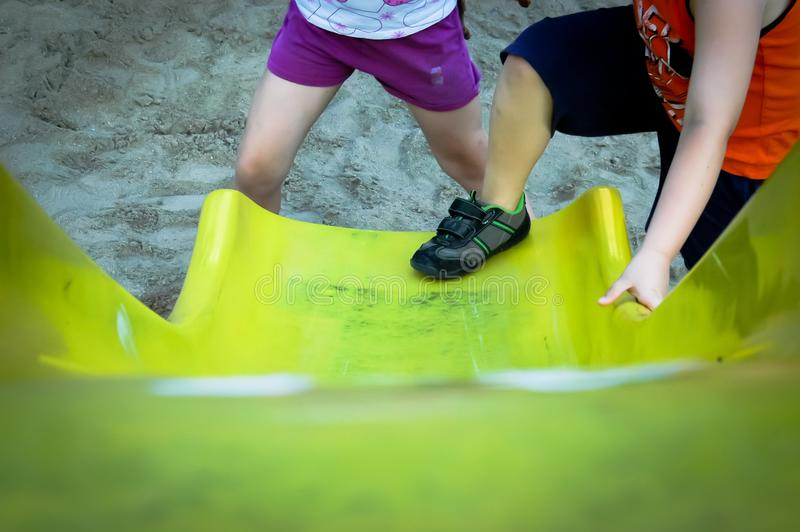 Flicka och pojke som spelar på gul glidbana royaltyfri fotografi