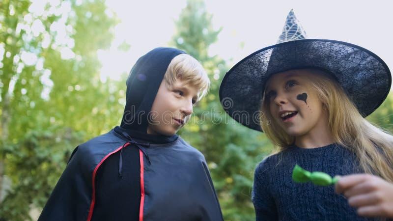 Flicka och pojke som tillsammans räknar godisar efter trick-eller-behandlande händelse och att ha gyckel arkivbilder