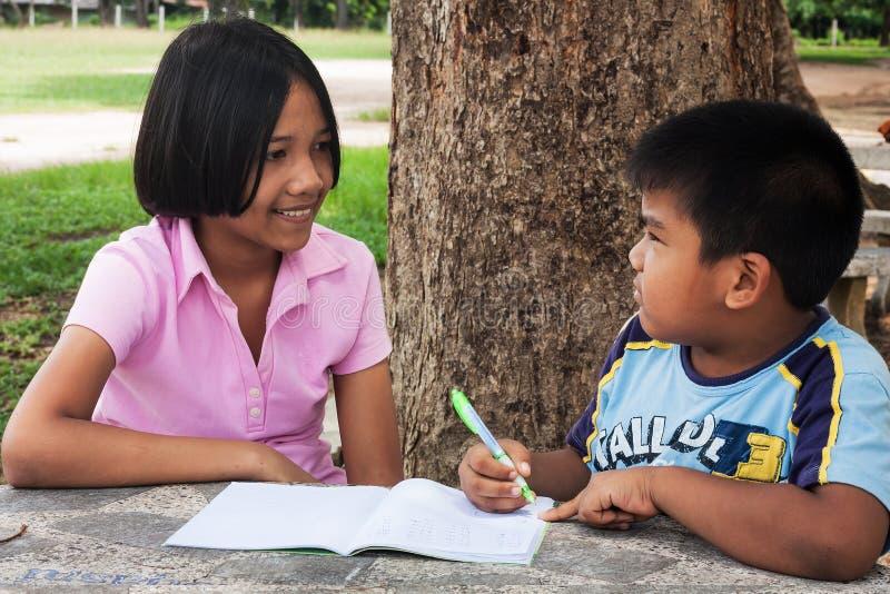 flicka- och pojkehandstil bokar i trädgården arkivbilder