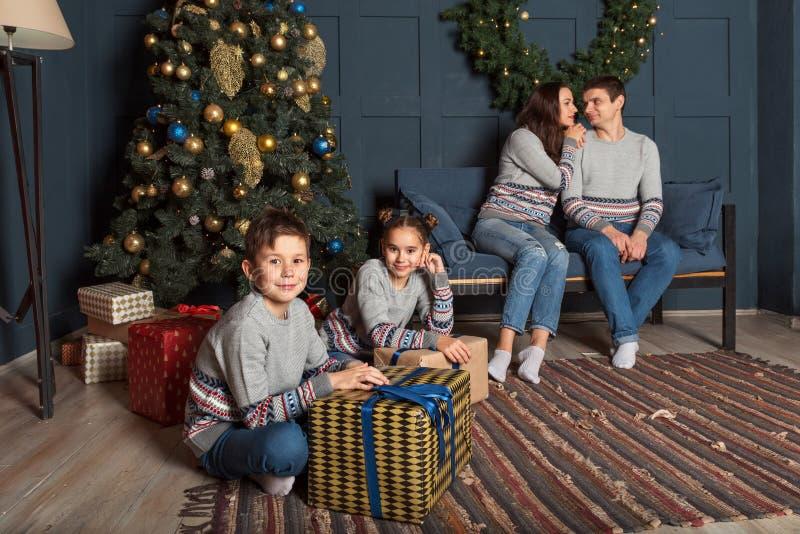 Flicka- och pojkesyskonet i familj ser sitta med gåvor framme av nytt års dekorerade julgran med föräldrar i royaltyfri fotografi
