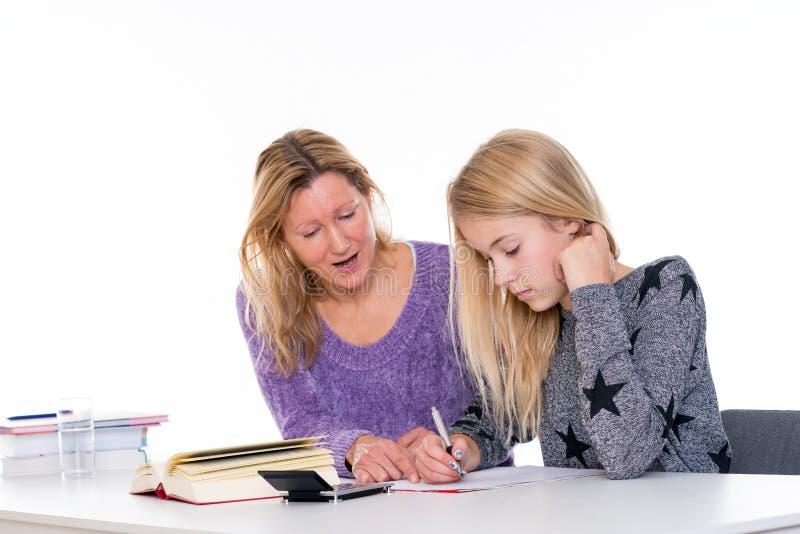 Flicka och samman med lärare i klassrumet arkivbild