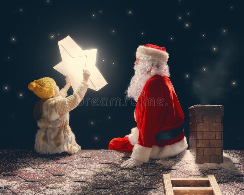 Flicka- och Santa Claus sammanträde på taket arkivfoto