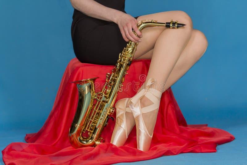 Flicka och saxofon arkivbild