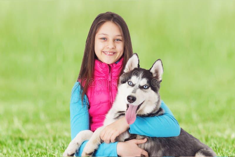 Flicka och Siberian skrovligt på det gröna gräset arkivbild
