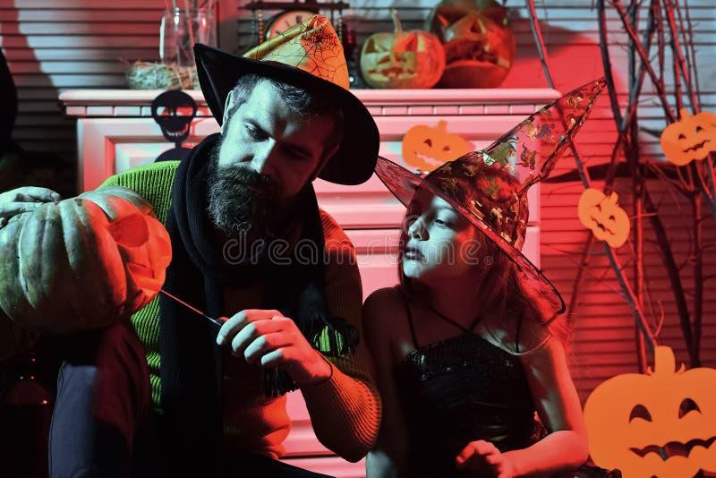 Flicka och skäggig man med allvarliga framsidor i karnevalrum royaltyfri bild