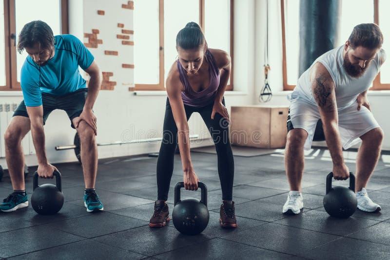 Flicka och två grabbar som lyfter vikter i konditionklubba arkivfoton