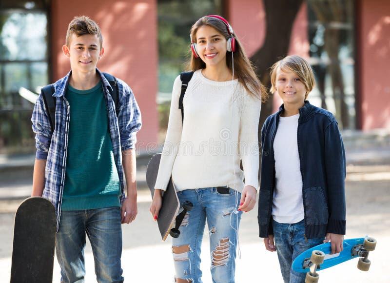 Flicka och två pojkar med skateboarder royaltyfri foto