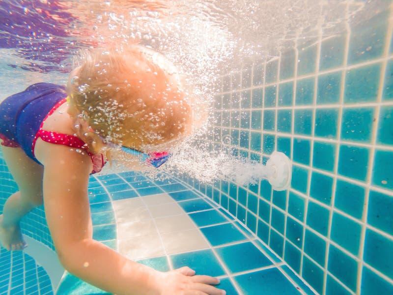 Flicka och under-slut för avrinning för vattenpöl arbetande upp arkivfoto