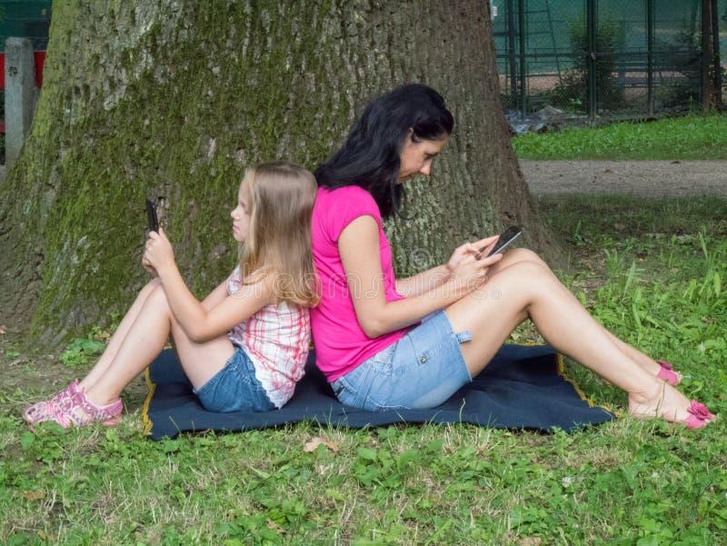 Flicka och ung kvinna som använder minnestavlan royaltyfri bild