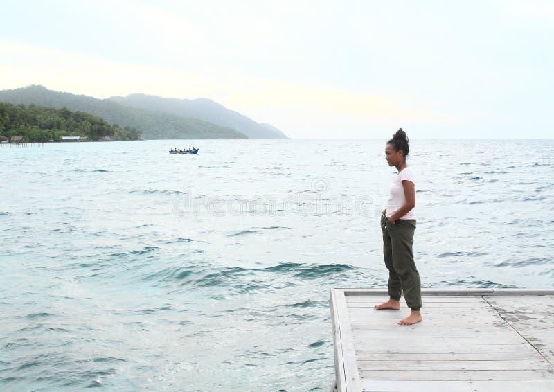 Flicka på bryggan vid havet arkivfoton
