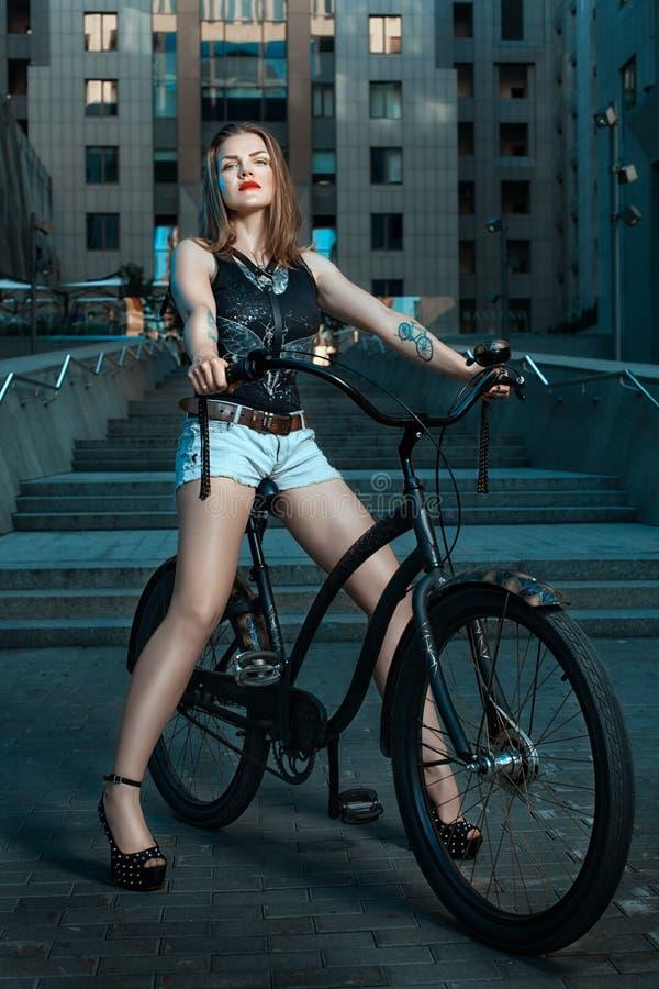 Flicka på cykeln på natten royaltyfria foton