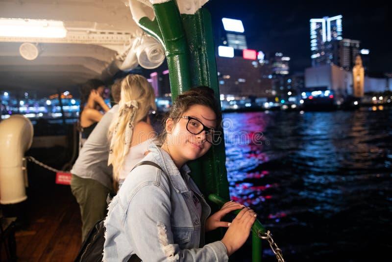 Flicka på den berömda stjärnafärjan Hong Kong som ser högert, natt, partisk inre för hamnsikt arkivfoto
