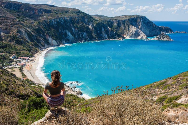 Flicka på det bästa mitt emot den Petani stranden på den Kefalonia ön, Grekland arkivbilder