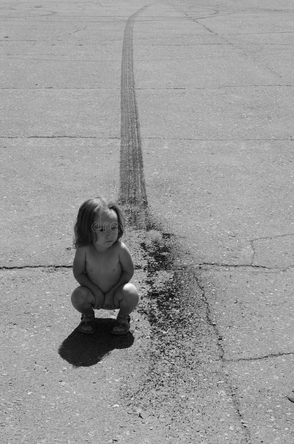 Flicka på en asfaltväg med sladdningfläckar arkivfoton