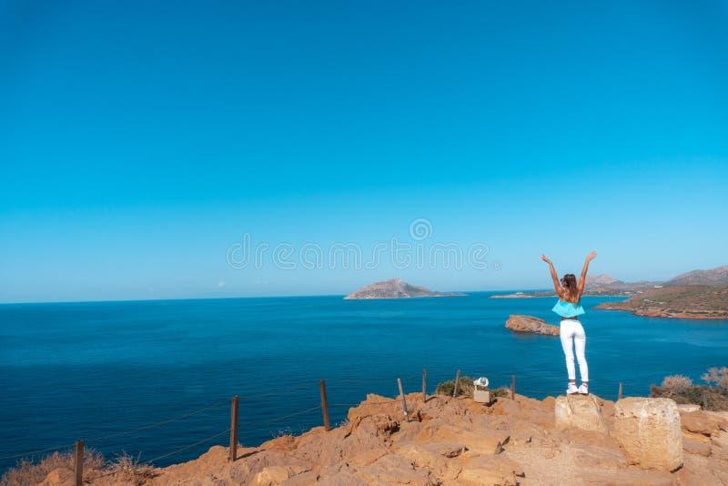 Flicka på en hög klippa ovanför havet arkivbild