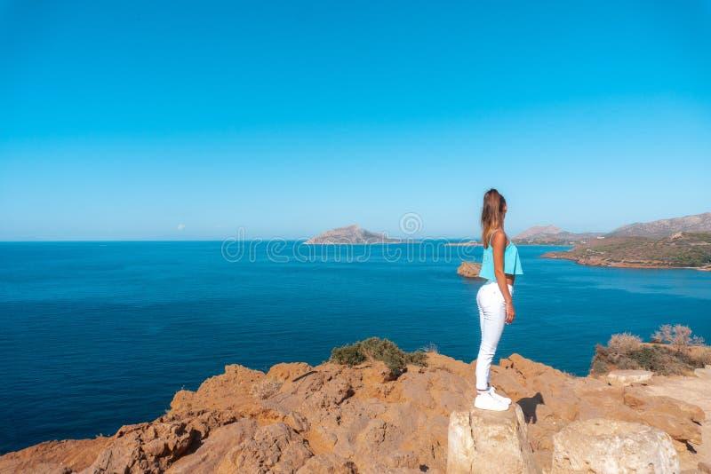 Flicka på en hög klippa ovanför havet royaltyfri bild