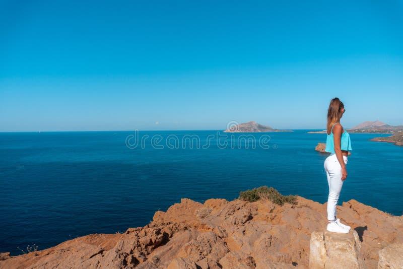 Flicka på en hög klippa ovanför havet royaltyfri fotografi