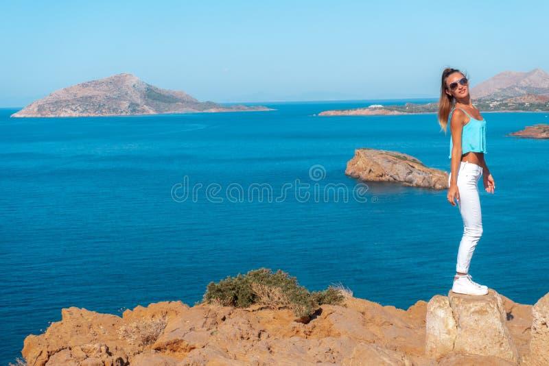 Flicka på en hög klippa ovanför havet royaltyfri foto